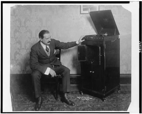 Man seated alongside phonograph, c. 1909. Library of Congress.
